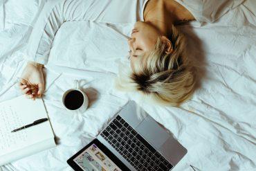 Person, die mit von sich gestreckten Armen auf einer weißen Bettdecke liegt. Oberhalb ihres Kopfes sind ein Laptop, eine Kaffeetasse und ein Stift zu sehen.