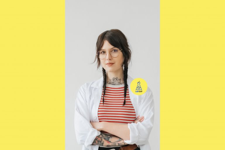 Host des Podcasts Lab Gap, Victoria Müller, trägt einen Laborkittel und blickt selbstbewusst in die Kamera.