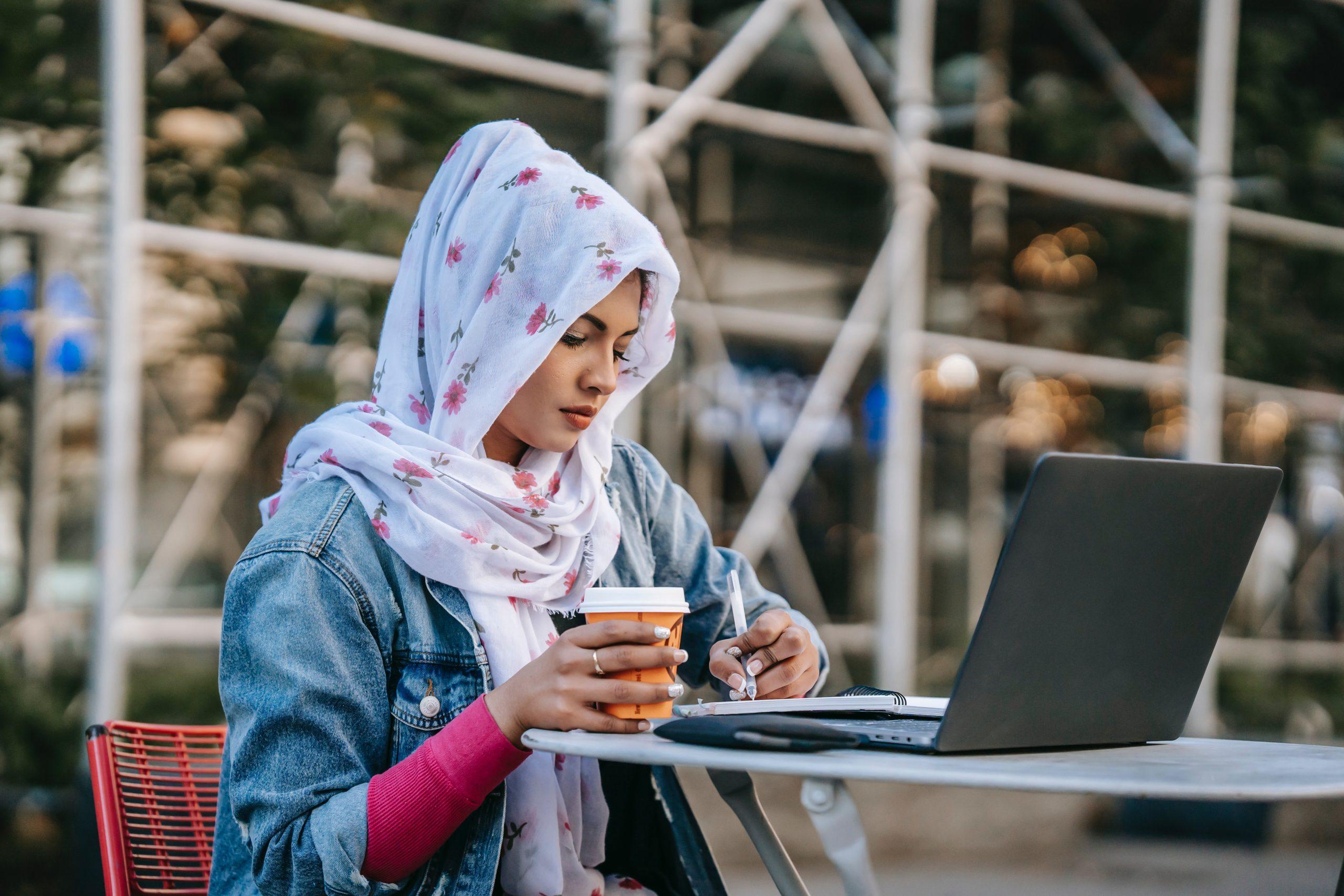 Eine Hijab tragende Frau sitzt mit einem Kaffeebecher in der Hand an einem Tisch und schaut in ihren Laptop.