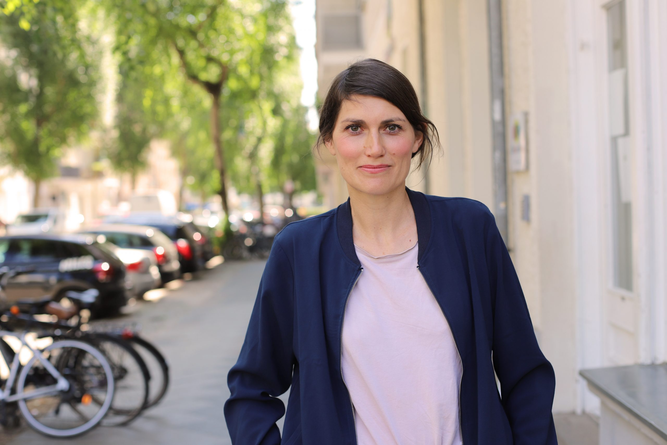 Auf dem Foto ist Lisa Seelig zu sehen, im Hintergrund ein Straßenzug.