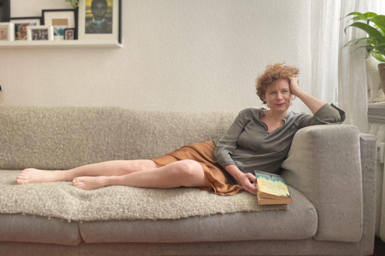 Auf dem Foto ist die Autorin Tina Molin zu sehen, die lächelnd und mit einem Buch in der Hand auf einem Sofa lehnt.