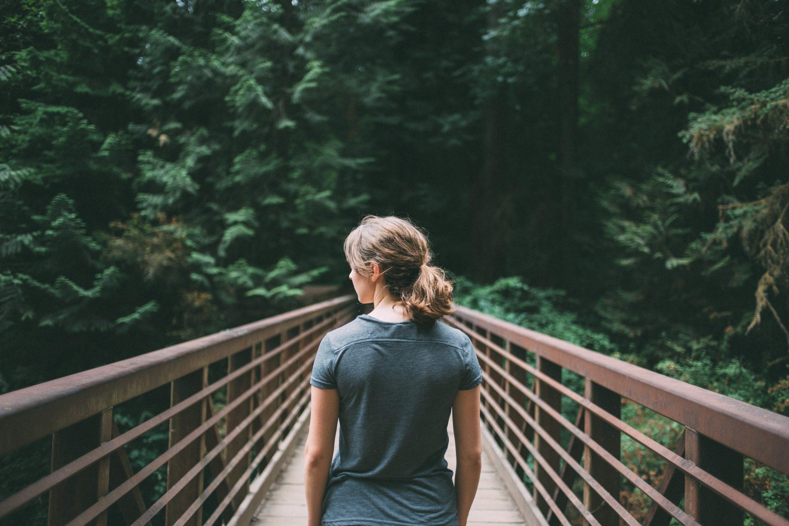 Eine Frau, von hinten zu sehen, geht über eine Brücke in Richtung Wald.