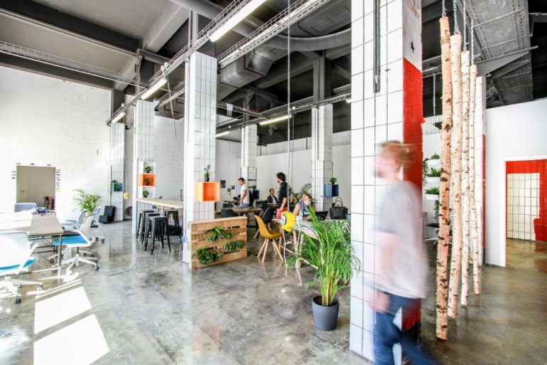 Auf dem Bild ist ein Coworkingspace mit Schreibtischen im Industrieambiente zu sehen.