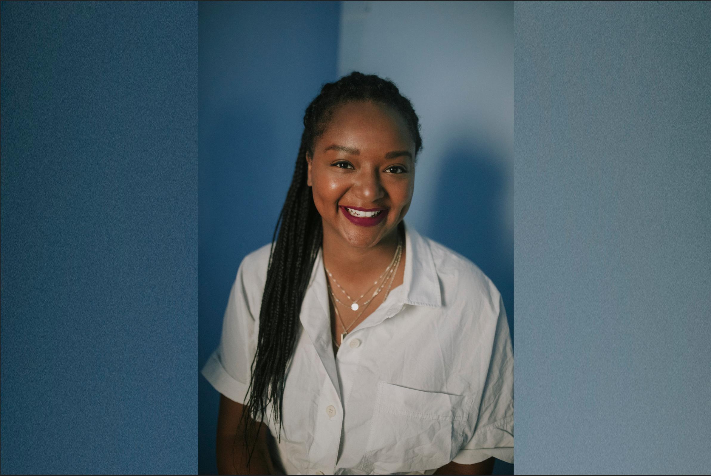 Auf dem Bild ist vor blauem Hintergrund die Politikerin Aminata Touré zu sehen.