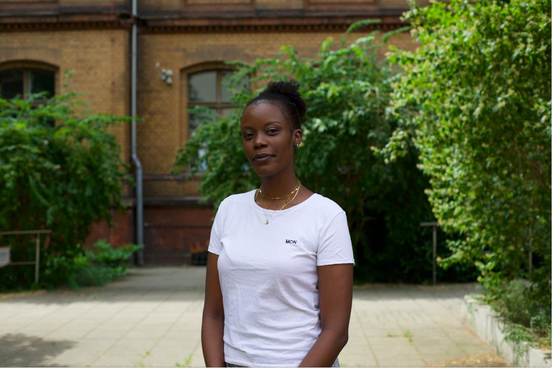 Auf dem Foto ist die Autorin Anna Dushime in einem weißen T-Shirt zu sehen. Sie steht in einem grünen Innenhof und blickt in die Kamera.