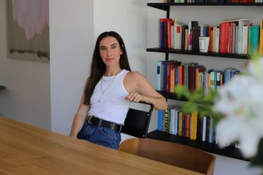 Auf dem Foto ist die Autorin Mirna Funk zu sehen, die an einem Holztisch sitzt und ernst in die Kamera blickt.
