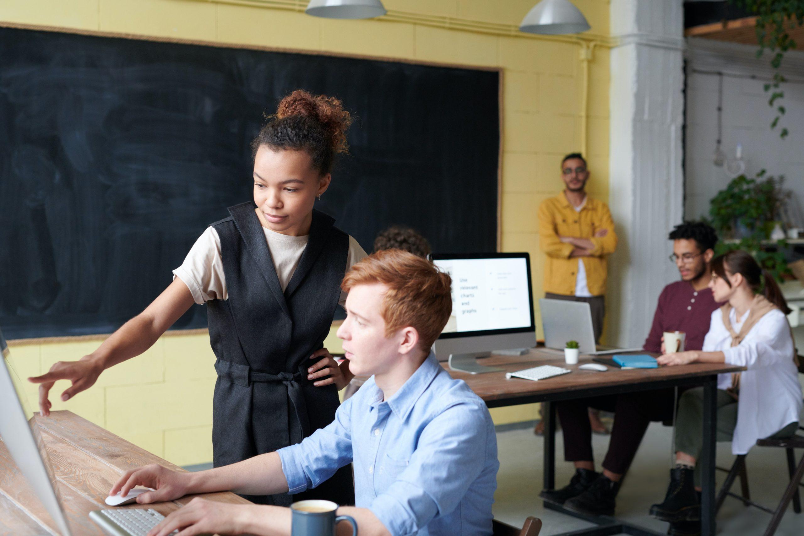 Ein Mann sitzt vor seinem Bildschirm, eine neben ihm stehende Frau zeigt auf den Bildschirm und erklärt etwas.