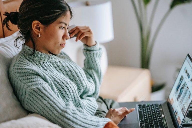 Eine Frau in einem türkisen Wollpullover blickt konzentriert auf ihren Laptopbildschirm.