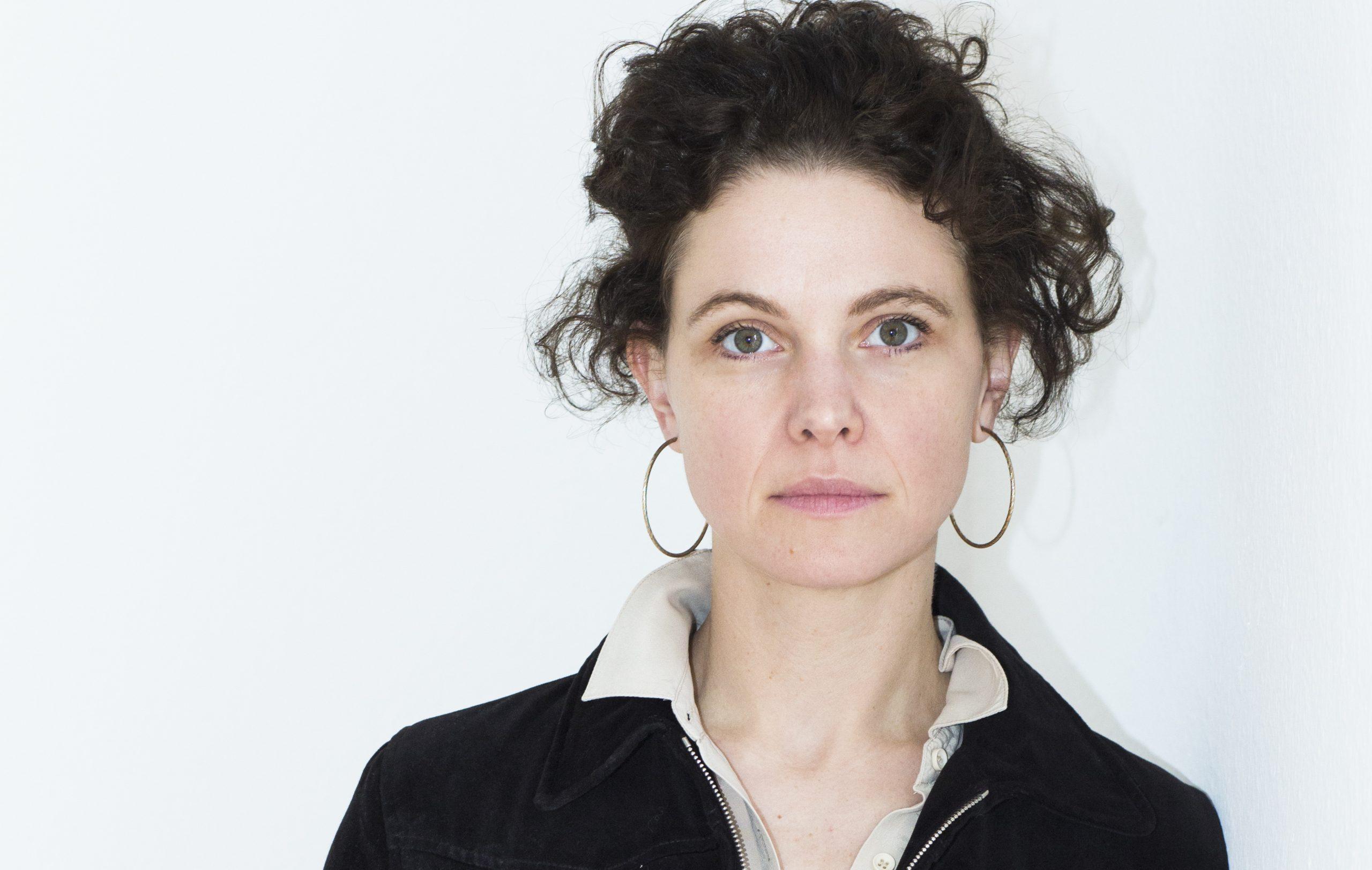Auf dem Foto ist die Autorin Caroline Rosales zu sehen, sie trägt ein weißes Hemd und ein schwarzes Jackett.