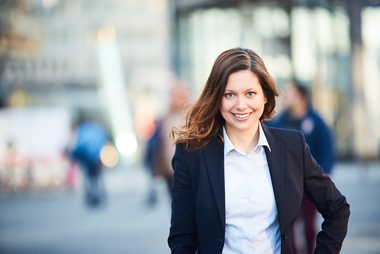 Eva Schulte-Austum läuft auf einer belebten Straße auf die Kamera zu und lächelt.