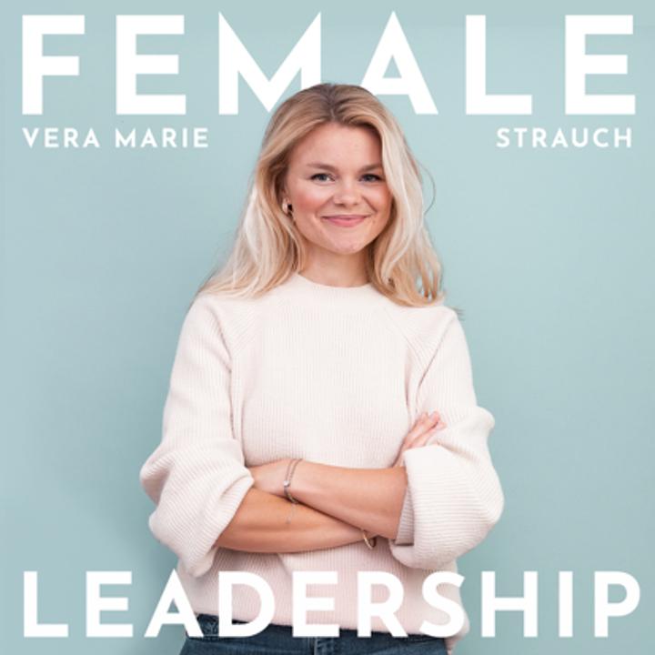 Vera Marie Strauch hat blonde Haare und steht mit verschränken Armen und einem Lächeln vor einer hellblauen Wand.
