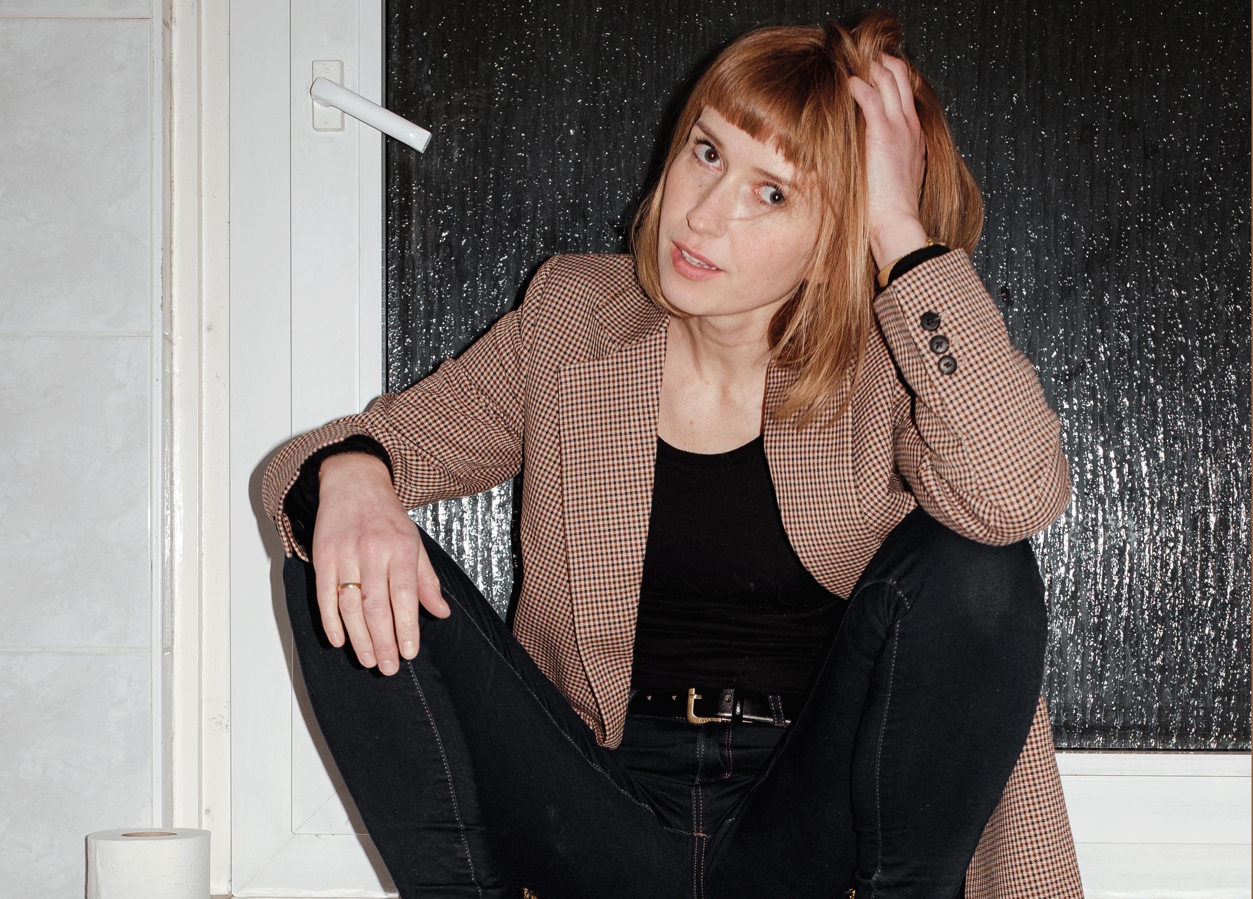 Katja Lewina sitzt mit Schuhen und Jacke auf einer Heizung neben einer Klopapierrolle.