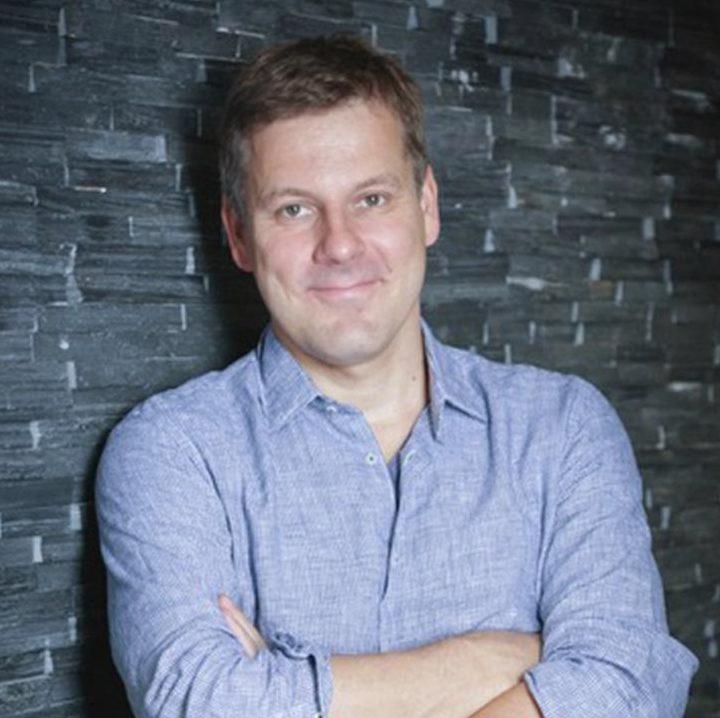 """Martin Hartmann, Professor für praktische Philosophie und Autor des Buches """"Vertrauen – Die unsichtbare Macht"""" steht vor einer Steinwand"""