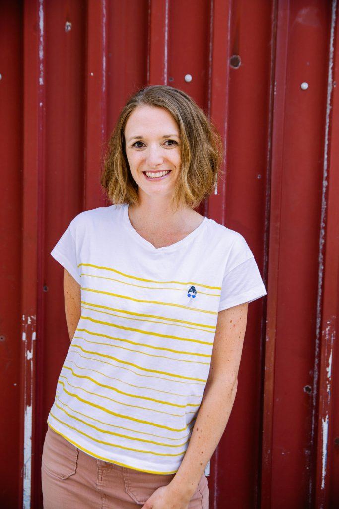 Podcasterin Madita Haustein steht vor einer roten Blechwand und lächelt in die Kamera.