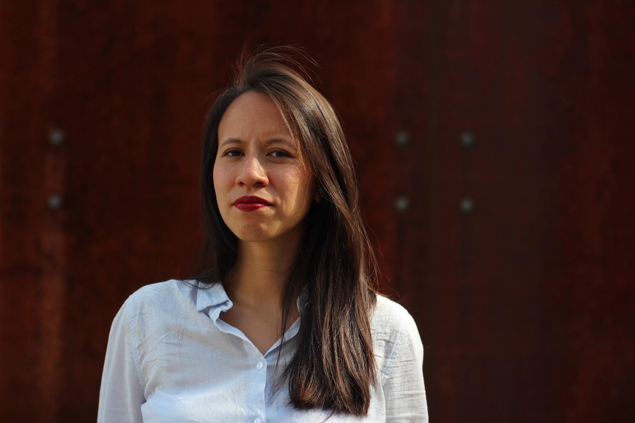 Auf dem Foto ist vor dunkelrotem Hintergrund die Autorin Thuy-An Nguyen zu sehen.