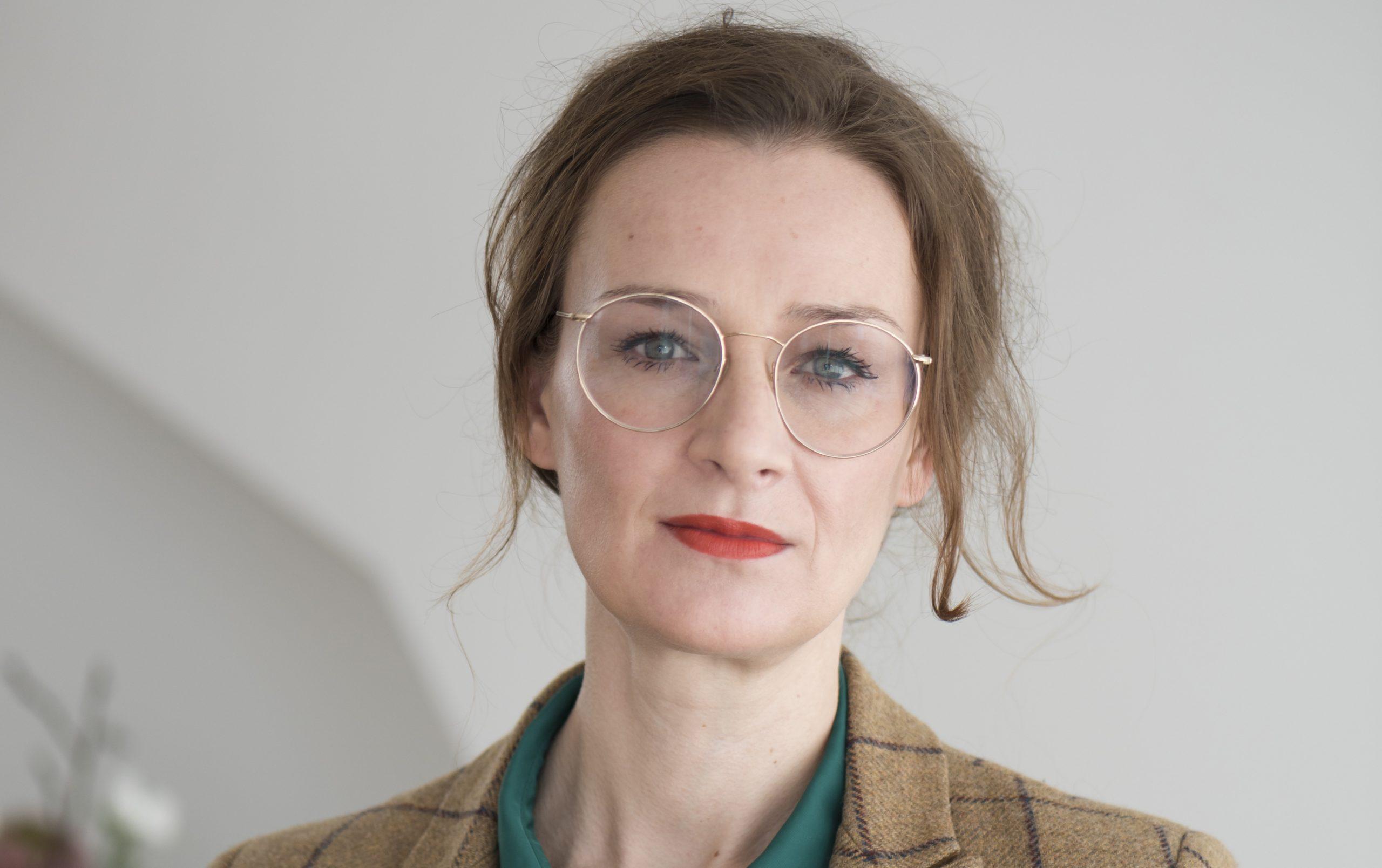 Auf dem Foto ist die Publizistin Franziska Schutzbach zu sehen, sie trägt eine flaschengrüne Bluse und einen karierten Blazer.
