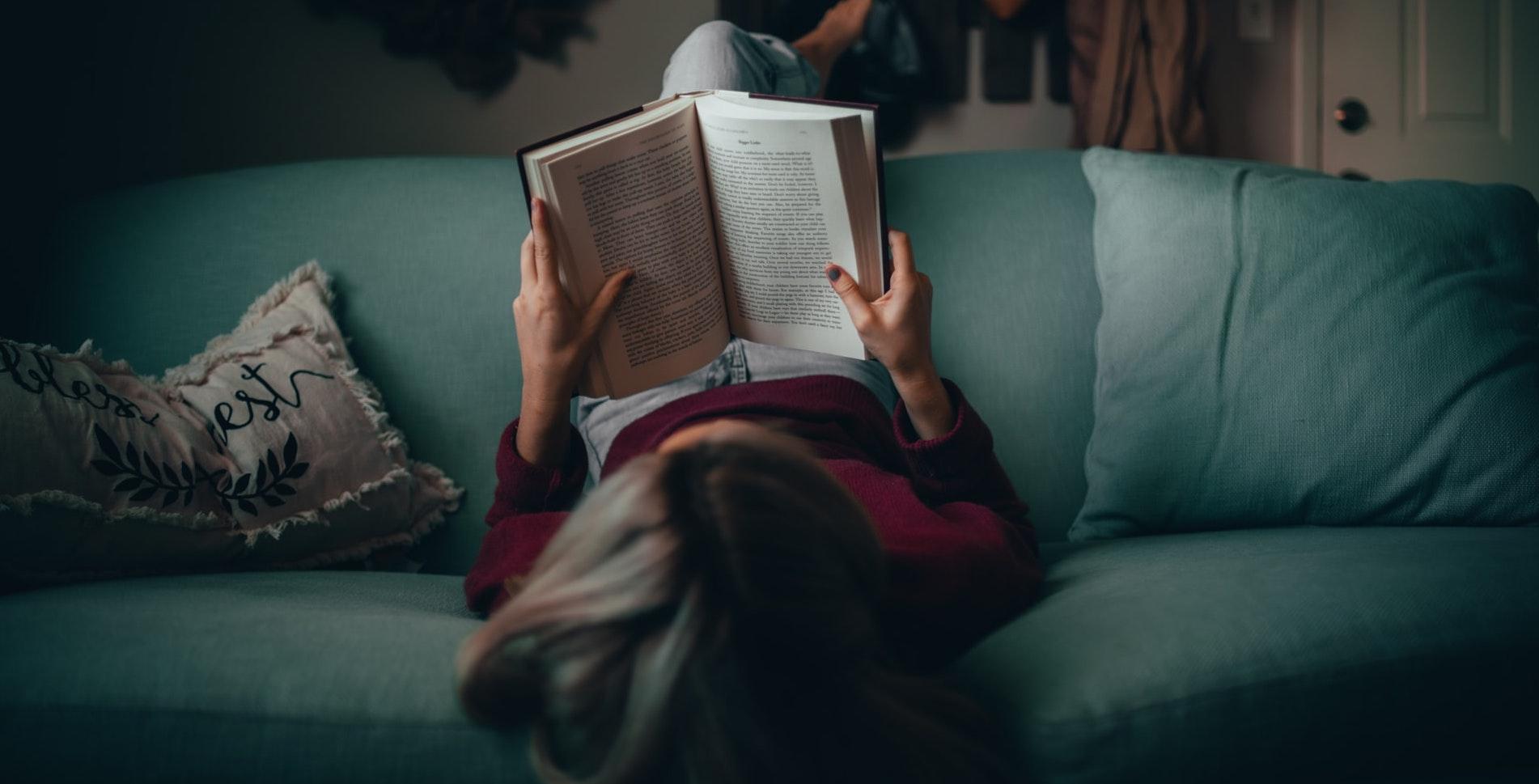 Auf dem Bild ist eine Frau von hinten zu sehen, die auf einem grünen Sofa liegt und ein Buch liest.
